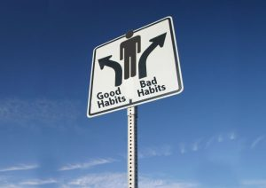 Sign with arrows pointing toward good habits and bad habits