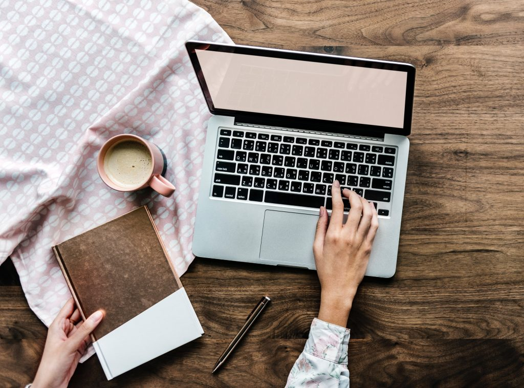 Woman using a laptop, cup of coffee and book