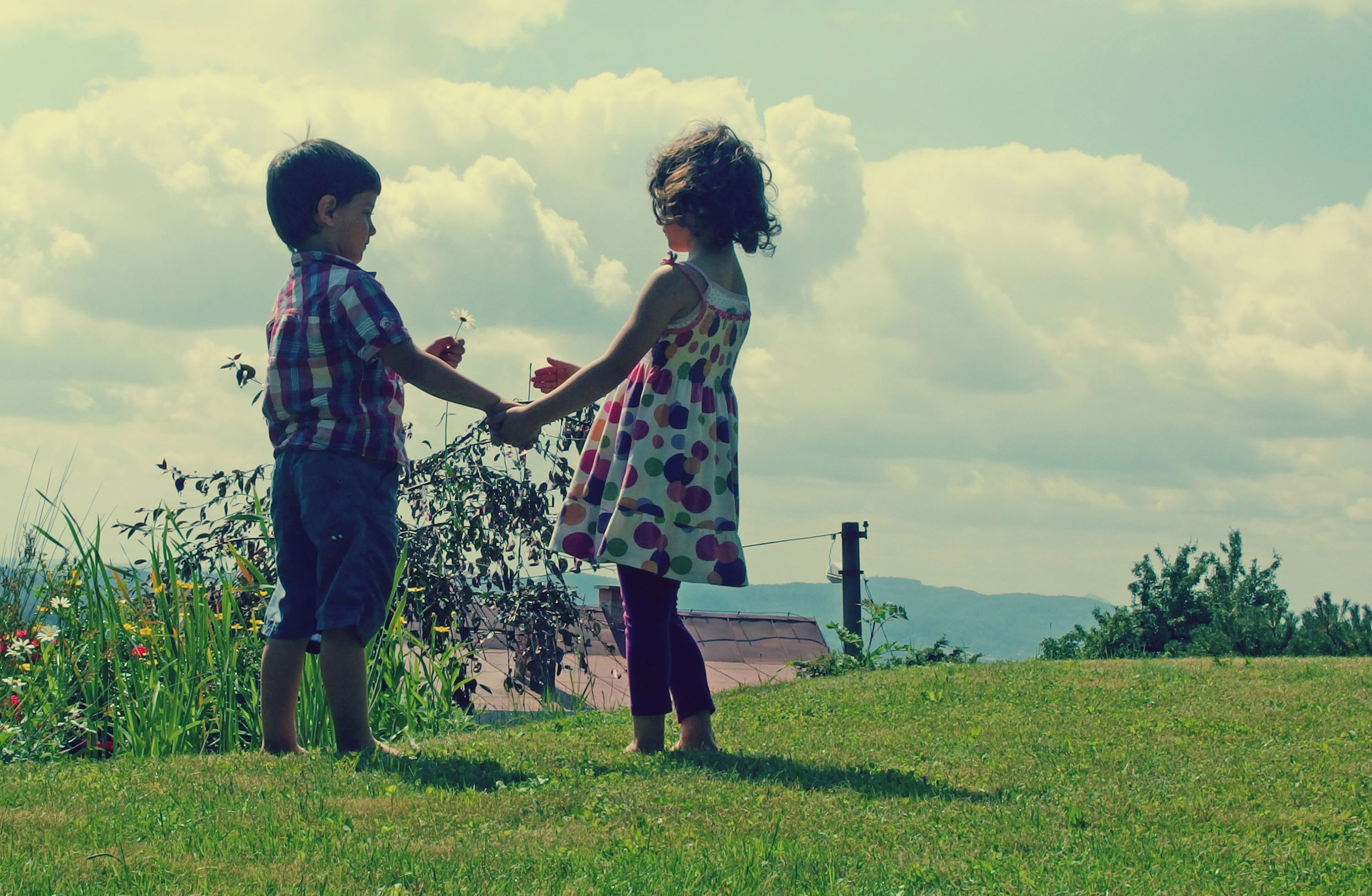 Little boy and girl standing in a field