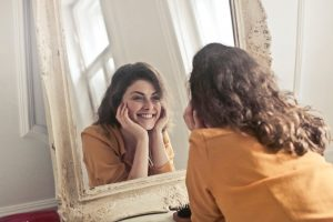 Woman looking in the mirror and smiling