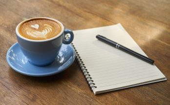 Cup of coffee, notebook, and pen