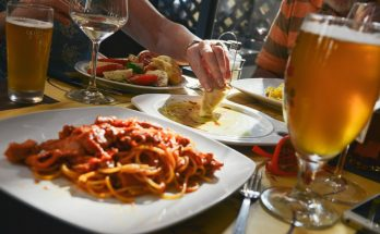 Table with Italian food and bear while a woman is eating