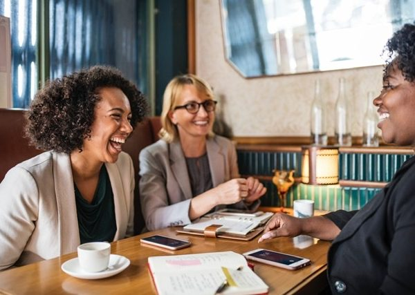 Three women laughing over coffee