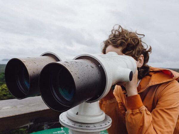 Woman looking through tourism binoculars