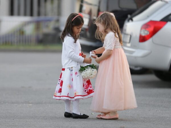 Two little girls in dresses with one helping the other with some flowers