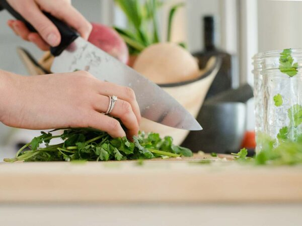 Woman cutting parsley with a chef's knife