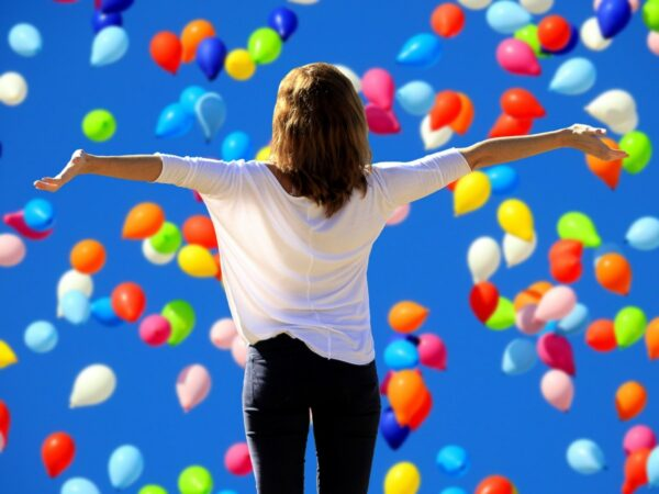 Woman celebrating with balloons falling around her